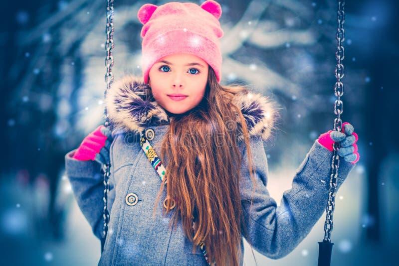 Charmig liten flicka på gunga i snöig vinter fotografering för bildbyråer