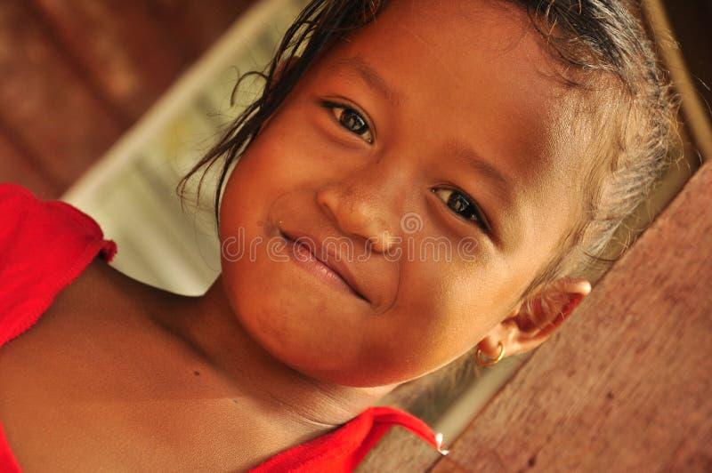 Charmig liten flicka som ler i byhuset arkivbilder