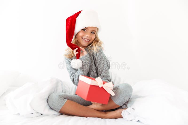 Charmig liten flicka som trycker på hennes ask för gåva för hatt för jultomten` s hållande, fotografering för bildbyråer