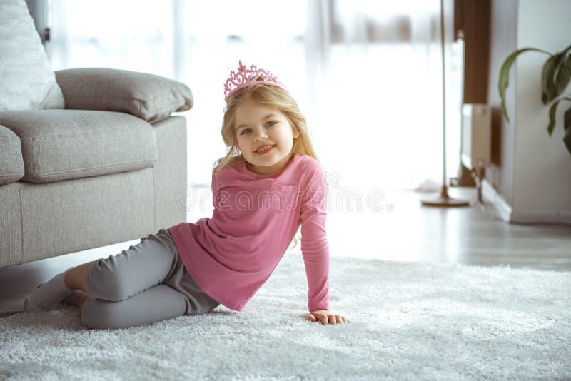 Charmig liten prinsessa som har gyckel i vardagsrum royaltyfria bilder