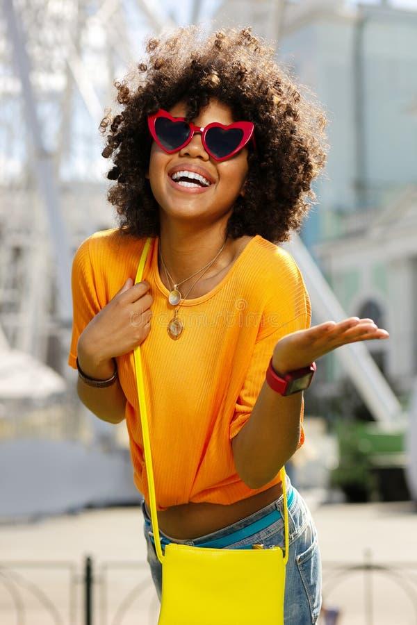Charmig lockig kvinna i hjärta-formad solglasögon som utstrålar lycka royaltyfri fotografi