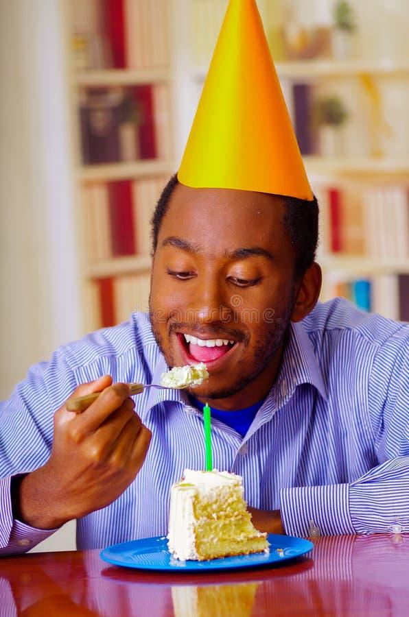 Charmig man som bär blått skjorta- och hattsammanträde av tabellen som äter det främsta stycket av kakan och att se lyckligt och  arkivfoto