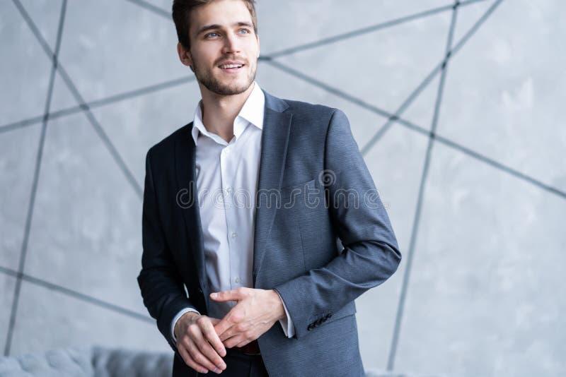 charmig man Stilig ung man i dräkten som ser bort och justerar hans omslag, medan stå inomhus fotografering för bildbyråer