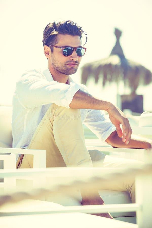 Charmig och attraktiv man med solglasögon som sitter och kopplas av i en stol i solen royaltyfri foto