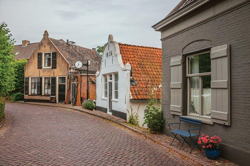 Charmig och tyst gata med lantliga hus för tegelsten och grönska i molnig dag på Drimmelen royaltyfri bild