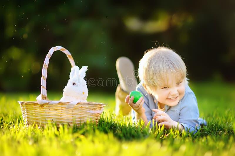 Charmig pysjakt för det easter ägget i vår parkerar på påskdag fotografering för bildbyråer