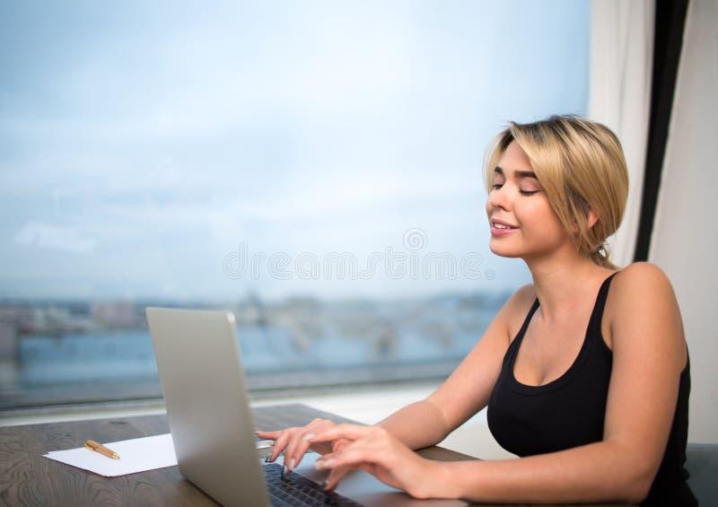Charmig skapare för kvinnawebsiteinnehåll som arbetar på den moderna bärbar datordatoren som i regeringsställning sitter mot föns royaltyfria bilder