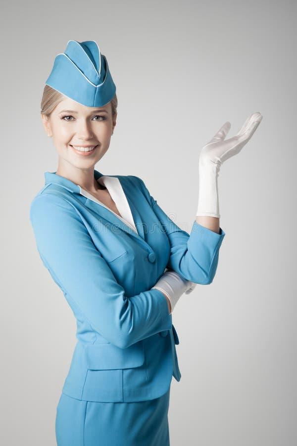Charmig stewardess In Blue Uniform som pekar på Gray Bac royaltyfria foton