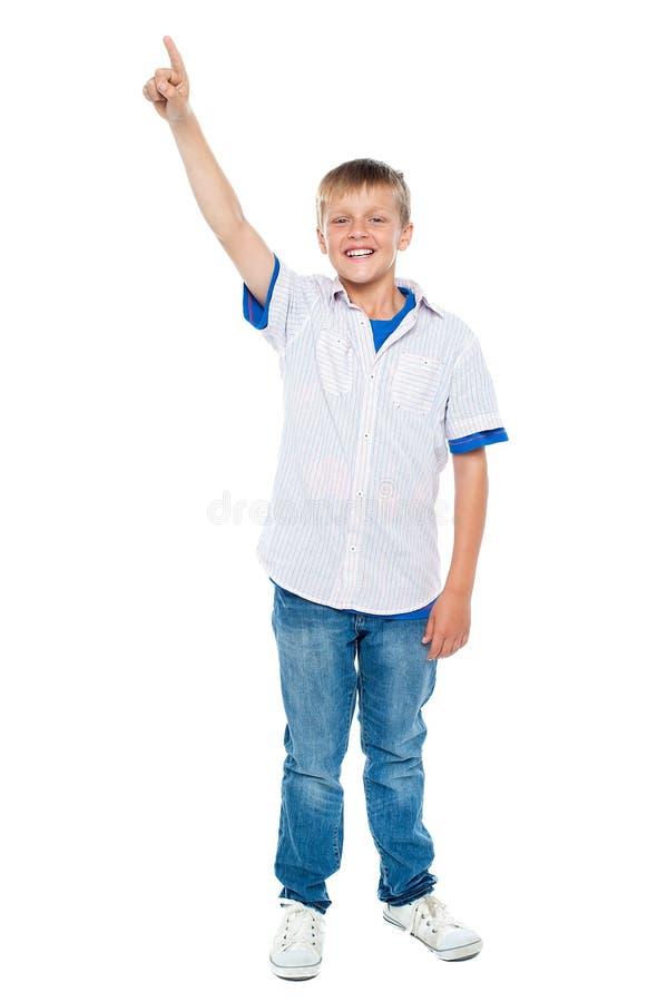 Charmig tillfällig pojke som uppåt pekar arkivfoton