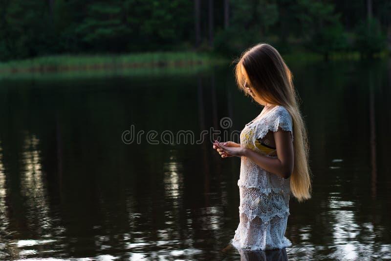 Charmig ung flicka i det vita klänninganseendet i vatten på solnedgång royaltyfri foto