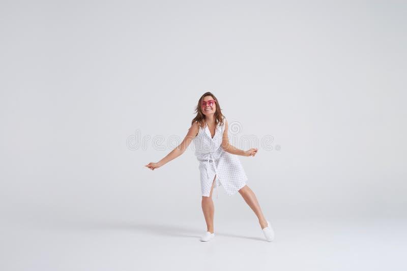 Charmig ung kvinna i klänningen som har gyckel på studion royaltyfri fotografi