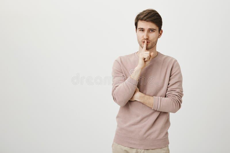 Charmig ung vuxen människa med brunt hår- och borstanseende med förförisk blick, medan visa shh underteckna över grå färger royaltyfri bild