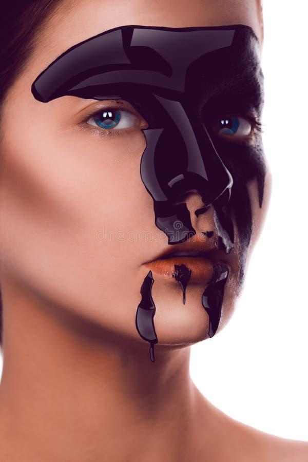 Charmig vuxen flicka med svart målarfärg på framsidan som ser kameran royaltyfri fotografi