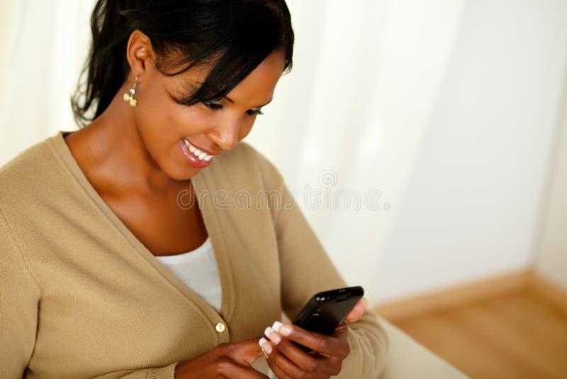 Charmig vuxen flicka som läser ett meddelande på mobiltelefon royaltyfria foton
