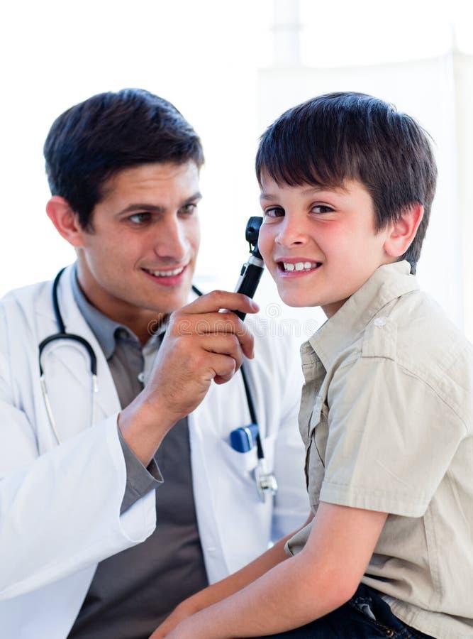 charmiga doktorsöron för pojke som undersöker little s royaltyfri foto
