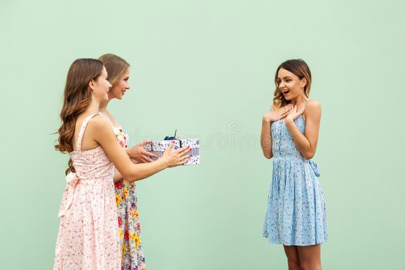 Charmiga flickor ger hennes härliga unga vuxna vän per gåva, ler under kvinnan och royaltyfri bild