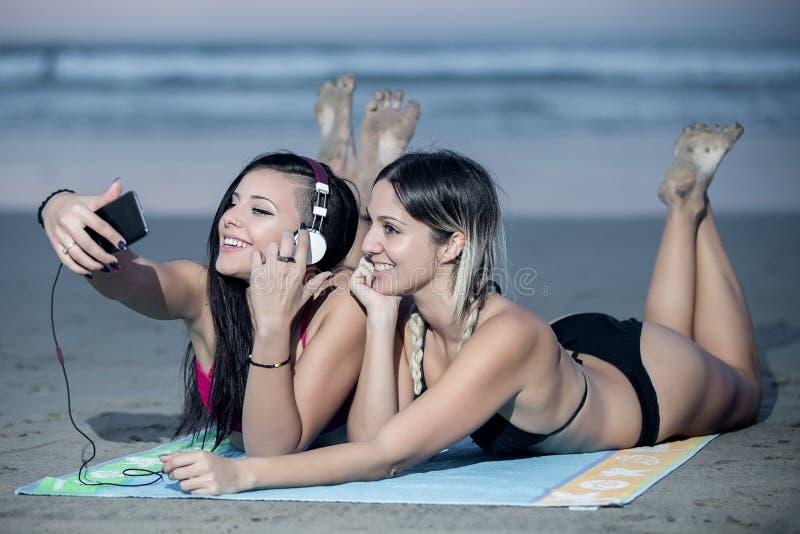 Charmiga flickvänner som tar selfie på stranden fotografering för bildbyråer
