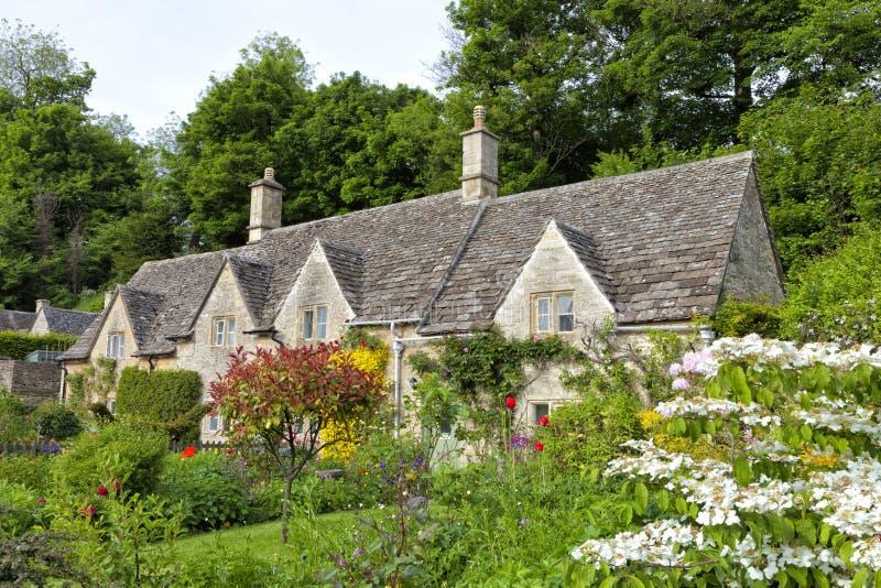 Charmiga gamla stenhus med härliga färgglade blommaträdgårdar royaltyfria bilder