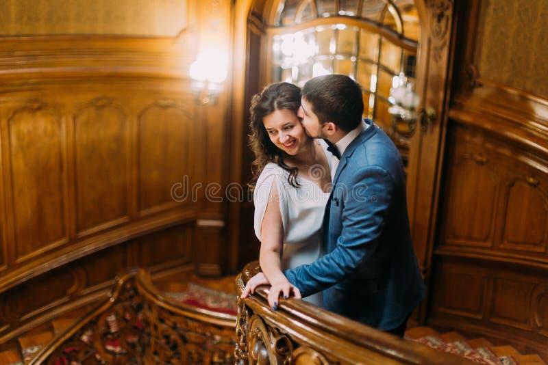 Charmiga nygift personpar som omfamnar att luta på balustraden på ursnygg antik trappa med bakgrunden av kungligt trä royaltyfria bilder