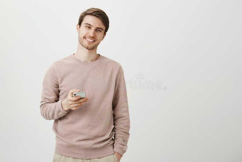 Charmigt angenämt ungt orakat mananseende med gulligt leende, den hållande smartphonen och att se kameran, medan vara över arkivfoton