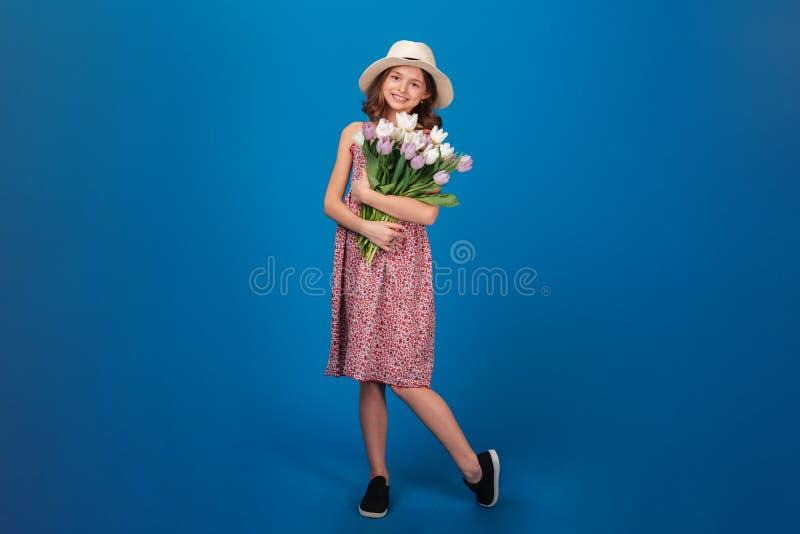 Charmigt gladlynt liten flickaanseende och hållande bukett av blommor fotografering för bildbyråer