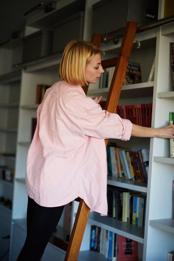 Charmigt kvinnaanseende för blont hår på stege på bokhyllan, medan välja boken arkivfoton