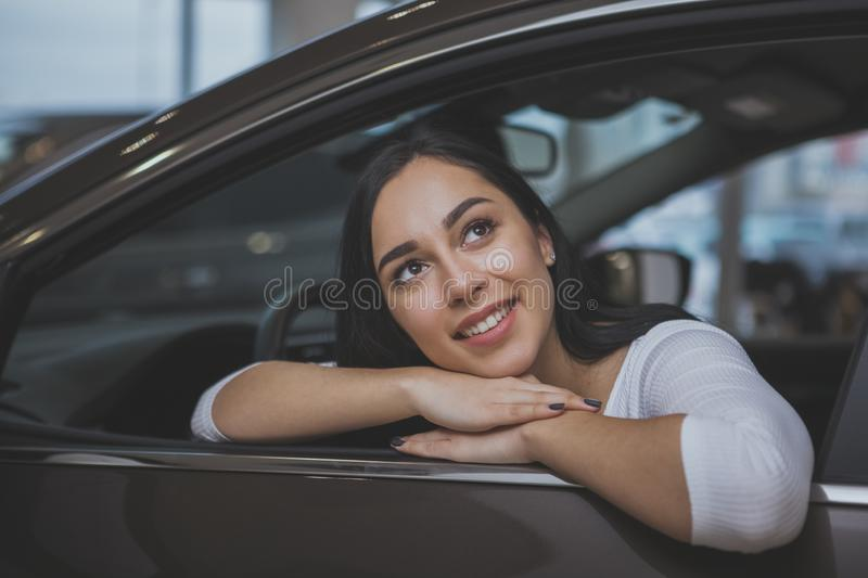 Lovely young woman buying new car at the dealership. Charmina young woman smiling, looking away dreamily from the window of a new automobile at the dealership stock image
