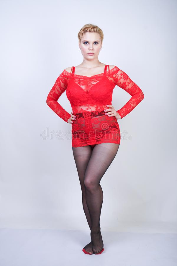 Charming adult blonde girl with short hair and a curvy body posing in a sexy lace blouse and black classic tights pantyhose with a stock photography