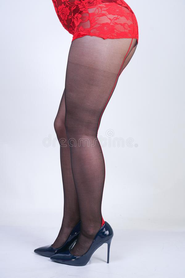 Charming adult blonde girl with short hair and a curvy body posing in a sexy lace blouse and black classic tights pantyhose with a. Red seam in the back on a royalty free stock images