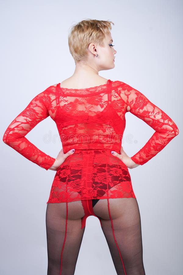 Charming adult blonde girl with short hair and a curvy body posing in a sexy lace blouse and black classic tights pantyhose with a. Red seam in the back on a royalty free stock photo