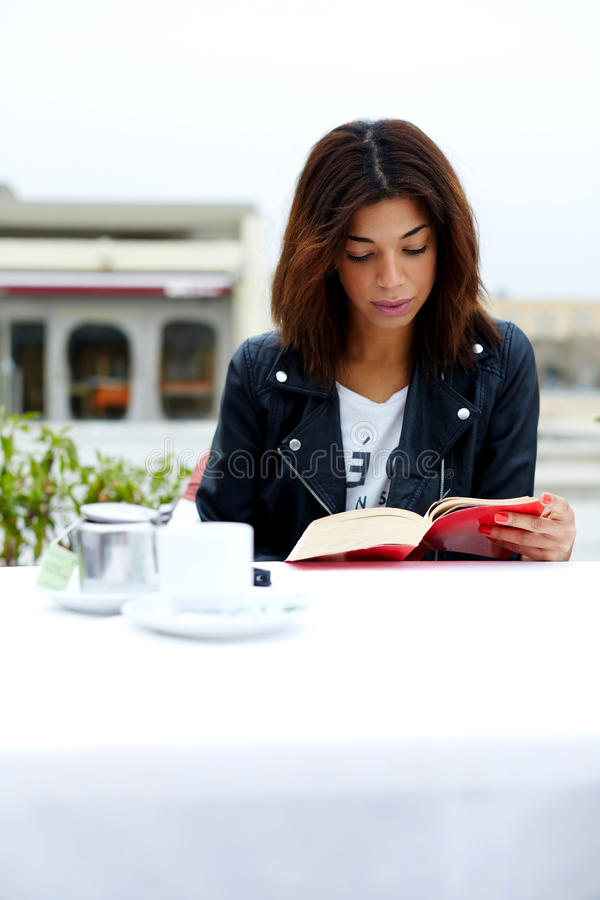 Charming afro american woman reading novel or book during her recreation time at weekend. Portrait of young lovely female enjoying a good book while sitting at stock photo