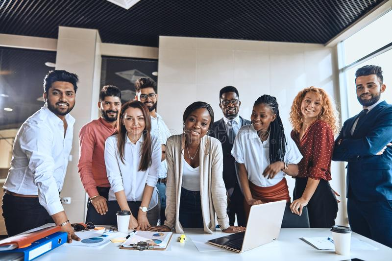 Charming afro boss leading young active diverse people stock images