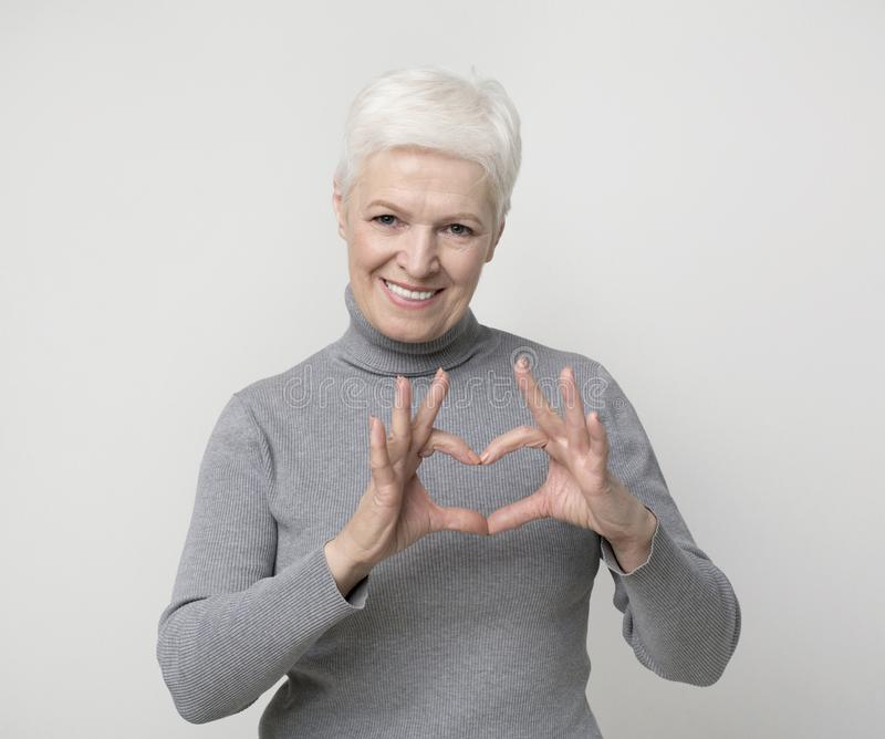 Charming aged woman showing heart gesture and smiling. Beautiful aged woman showing heart gesture and smiling on camera royalty free stock photos