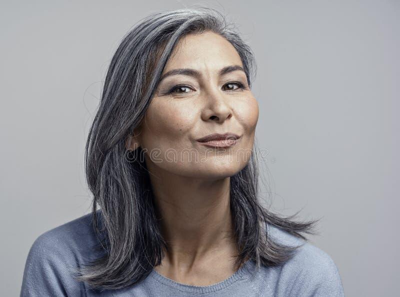 Charming Asian mature woman smiles at camera stock images