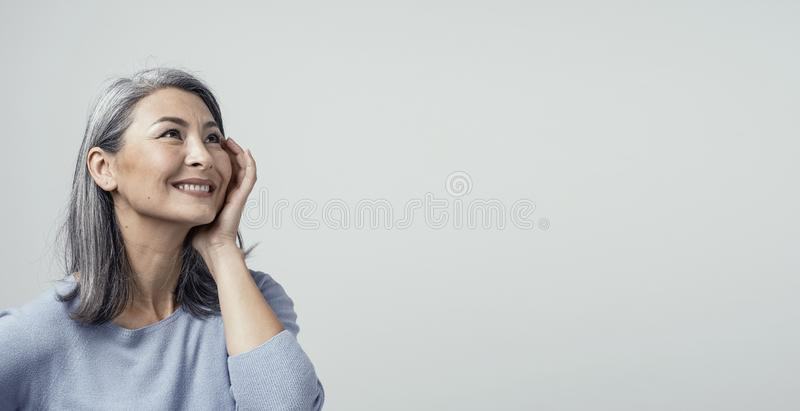 Side profile of charming asian woman smiling on white background royalty free stock photography