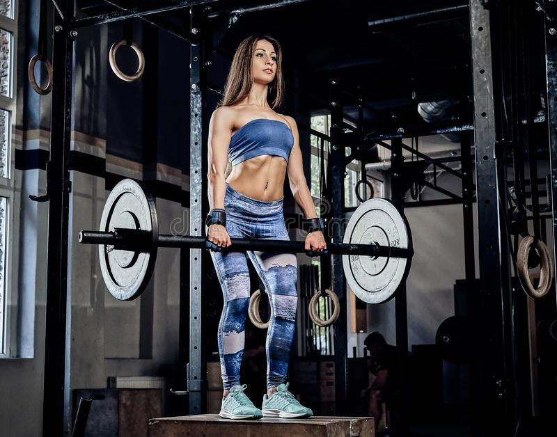 Charming athletic fitness woman wearing sports bodysuit posing with a barbell while standing on a sports pedestal in a. Beautiful athletic fitness woman wearing stock image