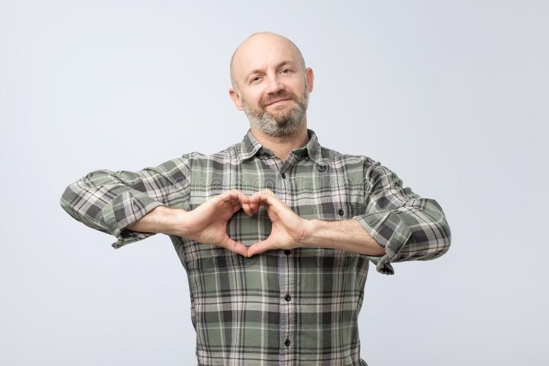 Charming attractive european man, holding hands in heart gesture royalty free stock image