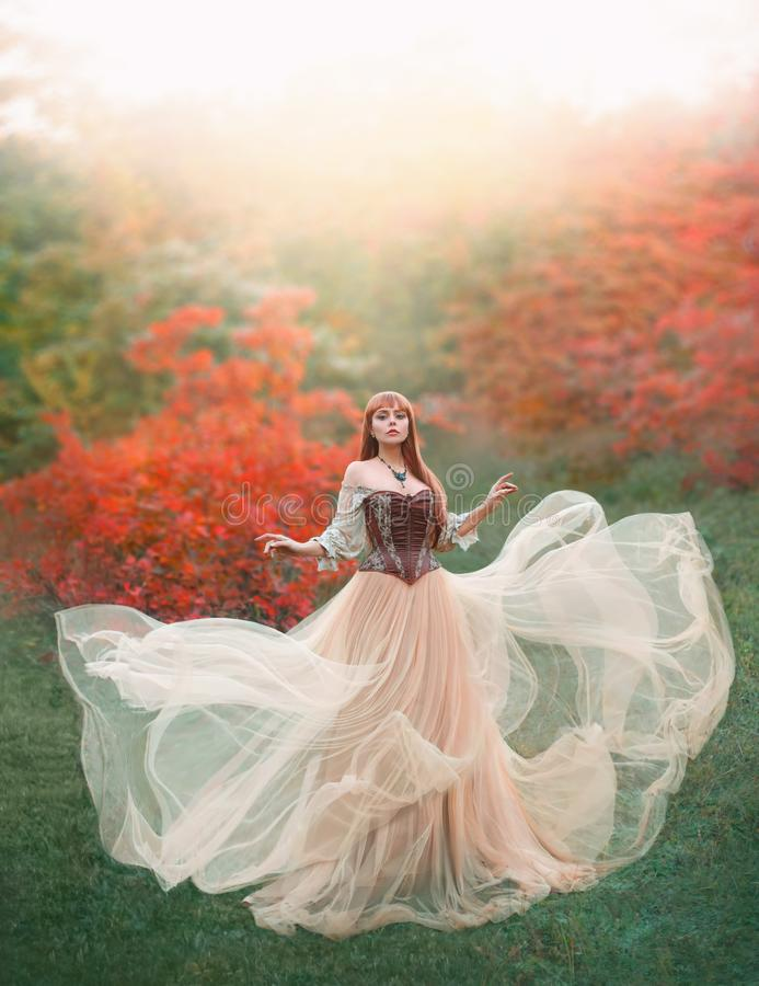 Charming attractive girl with long flying waving peach light vintage dress stands alone in forest, innocent lady looks stock photos