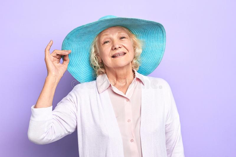 Charming, attractive old cheerful happy woman with blue stylish hat royalty free stock photos