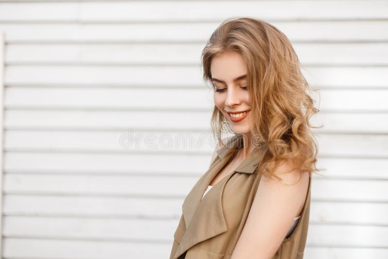 Charming attractive young woman with a beautiful smile in stylish summer clothes stands near a white wooden vintage wall outdoors royalty free stock images