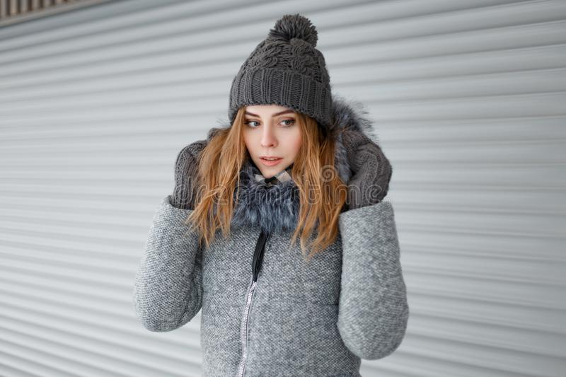 Charming attractive young woman in a gray vintage hat in a warm coat in knitted mittens posing near a white metal wall outdoors. royalty free stock photo