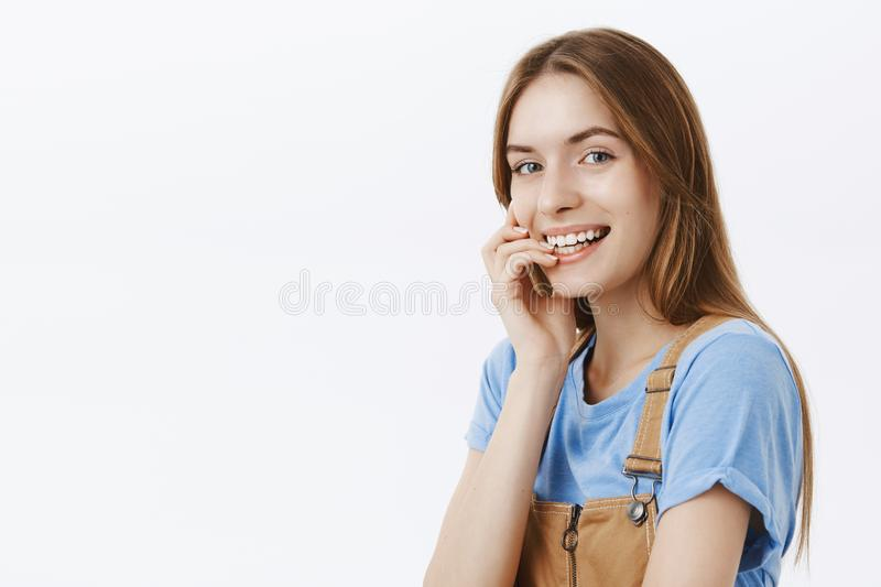 Charming authentic and enthusiastic charismatic young woman in t-shirt and overalls standing half-turned with flirty. Amused smile biting finger silly and stock photography