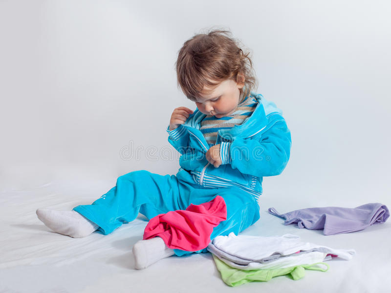 Charming baby in blue playing with baby clothes royalty free stock image