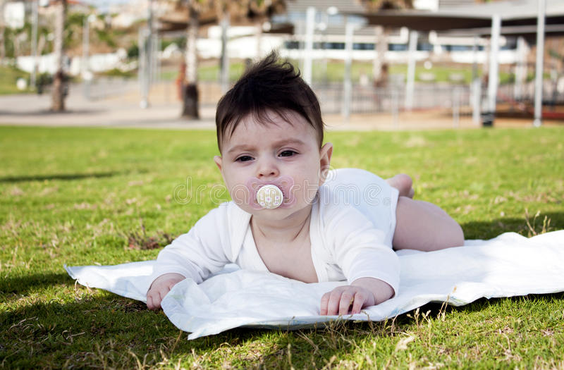 Charming baby girl with dummy lying on a green grass stock photography