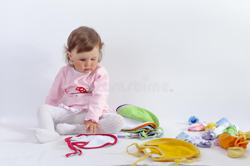 Charming baby in rose dress chooses bib stock photography