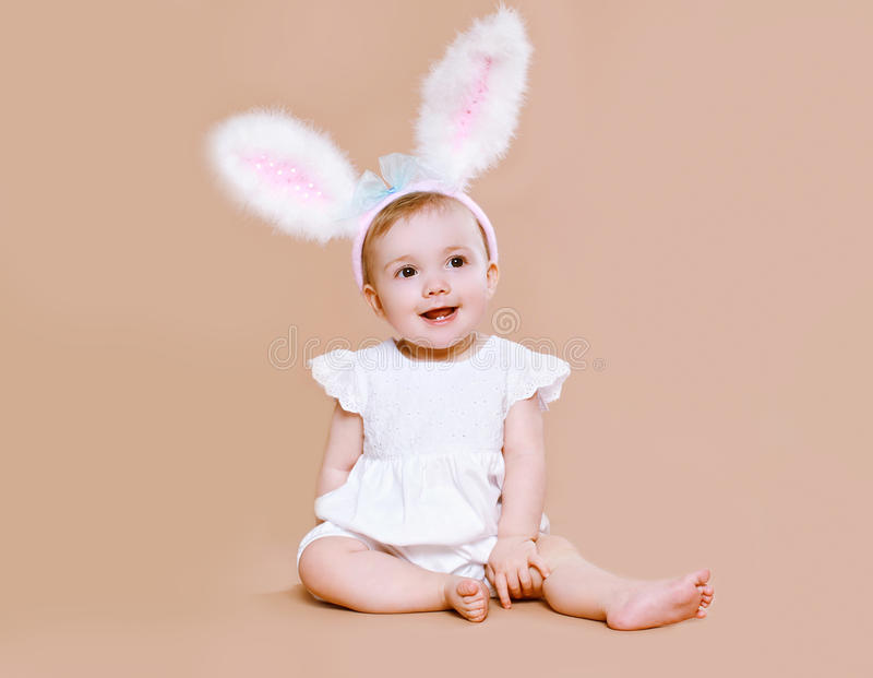 Charming baby sitting in costume easter bunny stock photography