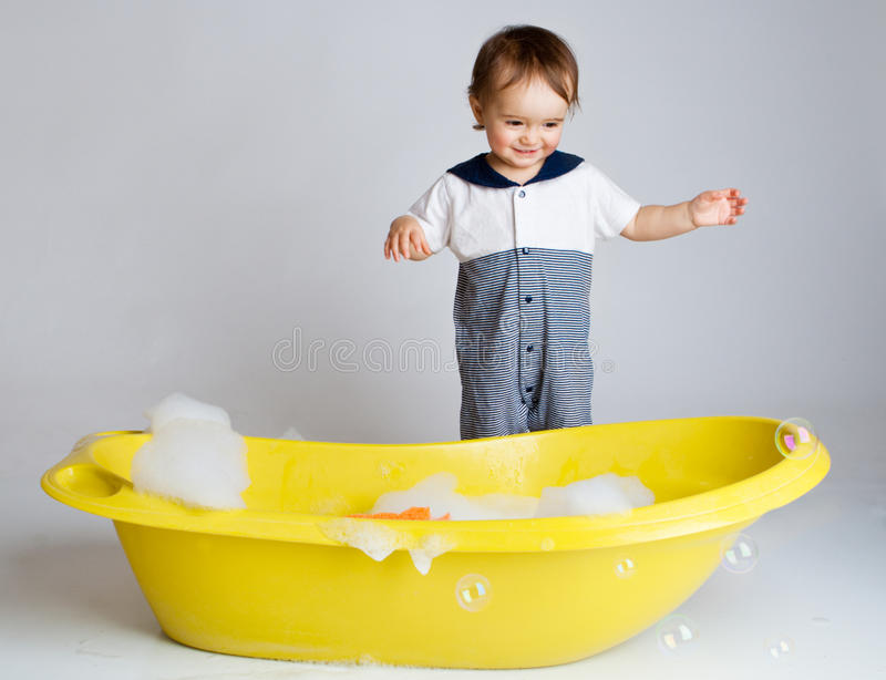Charming baby standing near bathtub stock photo