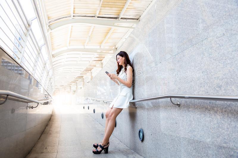 Charming beautiful asian woman. Attractive beautiful girl is listening nice music by using smartphone, earphone at walkway while stock photo