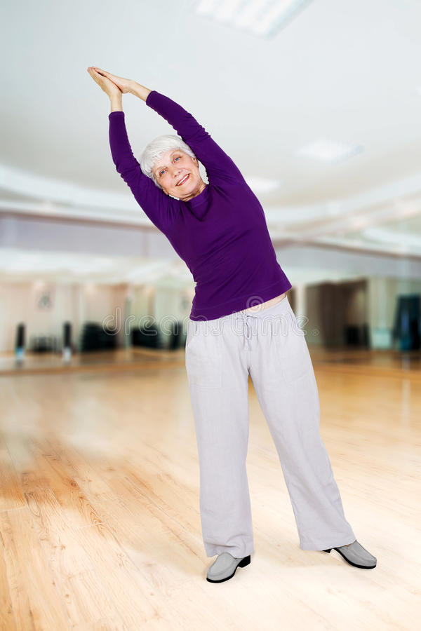 Charming beautiful elderly woman doing exercises while working out playing sports royalty free stock photography