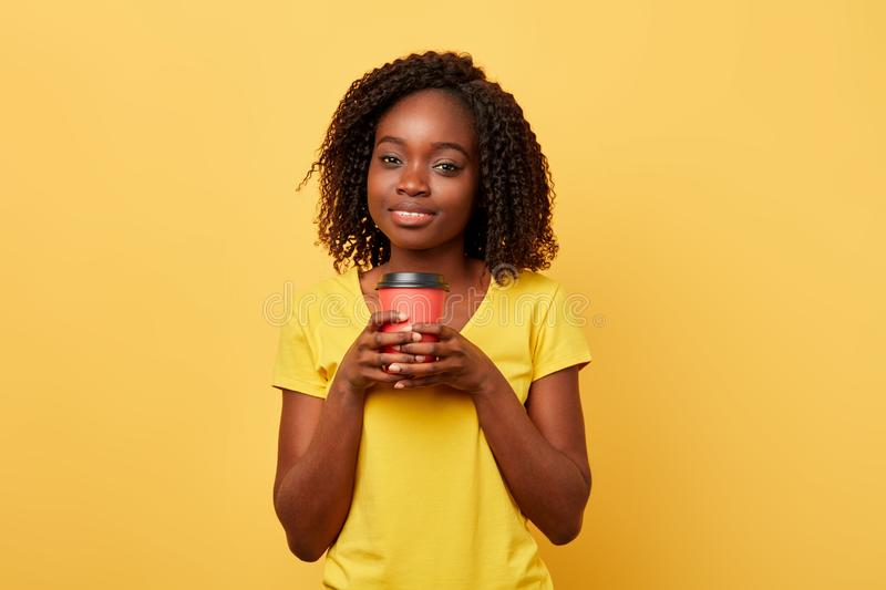 Charming beautiful girl holding takeaway coffee or tea from paper cup stock image